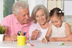 Portret van weinig leuk meisje met grootouders die bij de lijst trekken royalty-vrije stock afbeeldingen