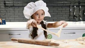 Portret van weinig mooi meisje in chef-kokhoed het spelen met deeg, Jong geitjekok in echte keuken 4K stock video