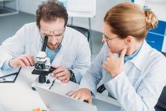 portret van wetenschappelijke onderzoekers in witte lagen die bij werkplaats met microscoop samenwerken stock foto's
