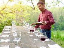 Portret van wijnproducent die rode wijn gieten in wijnglazen Stock Fotografie