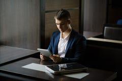 Portret van zakenman het zien op zijn tabletpc in koffie Royalty-vrije Stock Afbeeldingen