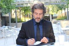 Portret van Zakenman Writing een Administratie buiten het Bureau royalty-vrije stock foto