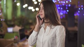 Portret van zeker in witte blouse formele slijtage die door cel mobiele telefoon spreken in moderne bureau of koffie Achtergrond stock video