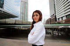 Portret van zekere Aziatische onderneemster die en zich camera tegen de stedelijke achtergrond van de de bouwstad bevinden bekijk Stock Fotografie