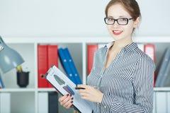 Portret van zekere bedrijfsvrouw die in glazen camera met klembord in handen bekijken Royalty-vrije Stock Foto