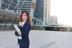 Portret van zekere jonge Aziatische bedrijfsvrouw met ringsbindmiddel die zich bij gang van stedelijke de bouwachtergrond bevinde Stock Fotografie