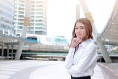 Portret van zekere jonge Aziatische onderneemster die en zich op camera stedelijke bouwstad met exemplaar ruimteachtergrond bevin Stock Afbeelding