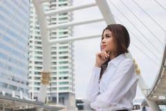 Portret van zekere jonge Aziatische onderneemster die en zich ver weg op de stadsachtergrond bevinden kijken Het concept van de l Stock Foto's
