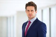 Portret van zekere jonge zakenman die kostuum in bureau dragen royalty-vrije stock afbeeldingen