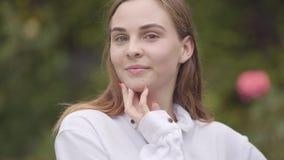 Portret van zekere onbezorgde mooie jonge glimlachende vrouw die met verschillende gekleurde ogen camera binnen bekijken stock videobeelden