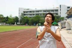 Portret van zich het jonge Aziatische atleet opwarmen en het uitrekken alvorens op een renbaan te lopen Royalty-vrije Stock Foto