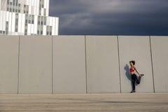 Portret van zich het jonge en aantrekkelijke vrouw uitrekken naast de muur in stedelijk park Royalty-vrije Stock Foto