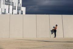 Portret van zich het jonge en aantrekkelijke vrouw uitrekken naast de muur in stedelijk park Royalty-vrije Stock Afbeelding