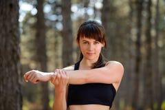 Portret van zich het Jonge Geschiktheidsvrouw Uitrekken in de Pijnboom Forest Female Runner Doing Stretches Gezond levensstijlcon Royalty-vrije Stock Foto's
