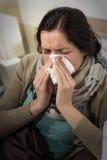 Portret van zieke vrouw die haar neus blazen Royalty-vrije Stock Afbeeldingen