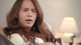 Portret van zieke vrouw thuis Jonge vrouw die in slaapkamer hoesten stock videobeelden