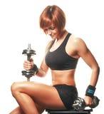 Portret van zitting en de holding van de roodharige de jonge vrouwelijke atleet dum Royalty-vrije Stock Foto's