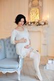 Portret van zwangere donkerbruine vrouw in een witte kleding in inte Royalty-vrije Stock Afbeelding