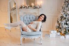 Portret van zwangere donkerbruine vrouw in een witte kleding in inte Royalty-vrije Stock Foto's