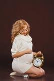 Portret van zwangere vrouw met klok in haar handen die op bruine achtergrond zitten Stock Afbeelding