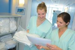 Portret 2 verpleegsters die wasserijlijst controleren bij het ziekenhuis Stock Fotografie