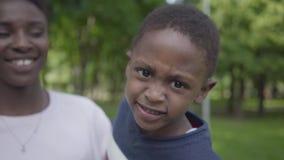 Portret vrij Afrikaanse Amerikaanse vrouw die haar grappige zoon in haar wapens in het groene park dicht tegenhouden Houdende van stock video