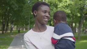 Portret vrij Afrikaanse Amerikaanse vrouw die haar zoon in haar wapens in het groene park dicht tegenhouden Leuke kind het bested stock videobeelden