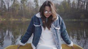 Portret vrij jonge vrouw die in modieus glazen en jeansjasje in de camera kijken Mooi landschap  stock videobeelden
