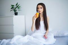 Portret vrij sexy jong meisje op bed in moderne flat in Th Stock Foto