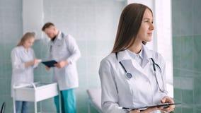 Portret vrouwelijke medische die specialist met stethoscoop door werkomgeving bij het ziekenhuis wordt omringd stock video