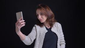 Portret w średnim wieku brunetki caucasian kobieta robi fotografiom na czarnym tle używać smartphone zbiory