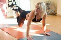 Portret w średnim wieku kobieta robi ćwiczeniom z pierścionkami w sprawności fizycznej centrum zdjęcie stock