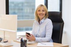 Portret W średnim wieku biznesowa kobieta pracuje przy biurem zdjęcia stock