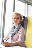 Portret w połowie dorosły bizneswomanu obsiadanie przy biurkiem w biurze Obrazy Royalty Free