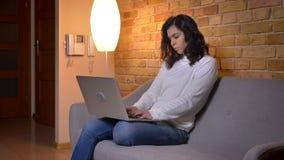 Portret w profilu baczny caucasian brunetka bizneswomanu obsiadanie na kanapie i działanie z laptopem w domu zbiory