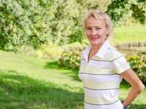 Portret w średnim wieku kobieta w parku Zdjęcia Stock
