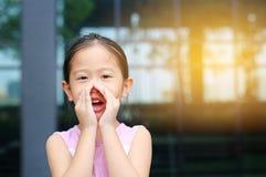 Portret weinig Aziatisch kindmeisje dat en door handen zoals megafoon handelt schreeuwt Communicatie concept stock afbeelding