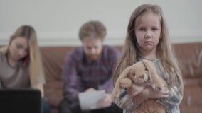 Portret weinig droevig ongelukkig meisje die met stuk speelgoed in handen in camera kijken Het jonge vrouw typen op haar laptop d stock videobeelden