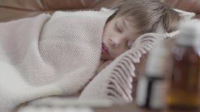 Portret weinig jongen die die op de bank liggen met een deken thuis wordt behandeld Het leuke kind rust r stock video