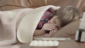 Portret weinig jongen die die op de bank liggen met een deken thuis wordt behandeld Het leuke kind rust De jongen is ziek, voelt  stock videobeelden