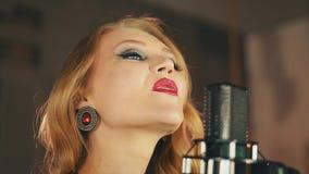 Portret wokalista z czerwonymi wargami wykonuje przy mikrofonem styl retro elegancja zdjęcie wideo