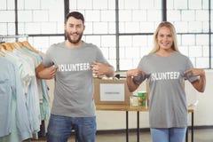 Portret wolontariuszi pokazuje ochotniczego tekst na tshirts Zdjęcie Stock