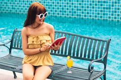 Portret Wychodząca młoda azjata dziewczyna patrzeje jej telefon komórkowego, mądrze telefonu ot pastylka siedzi na krześle obrazy royalty free