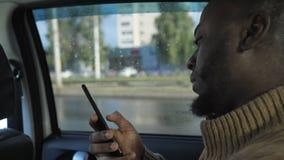 Portret wyszukuje smartphone murzyn jedzie samochód w deszczowym dniu w mieście zbiory