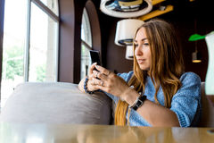 Portret of young female reading sms on the phone in cafe. Toned. Selective focus. Image of young female reading sms on the phone in cafe royalty free stock photography