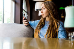 Portret of young female reading sms on the phone in cafe. Toned. Selective focus. Image of young female reading sms on the phone in cafe royalty free stock photo