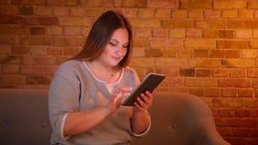 Portret z nadwagą długowłosy żeński freelancer pracuje attentively z pastylką w wygodnej domowej atmosferze zdjęcie wideo