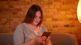 Portret z nadwagą długowłosy żeński freelancer pracuje przyjemnie z smartphone w wygodnej domowej atmosferze zdjęcie wideo