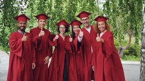 Portret z podnieceniem kończy studia uczeń wieloetniczna grupowa pozycja outdoors w czerwonych togach, deski i opowiadać zbiory