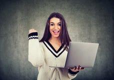 Portret z podnieceniem młodej dziewczyny mienia odświętności i laptopu sukces fotografia stock